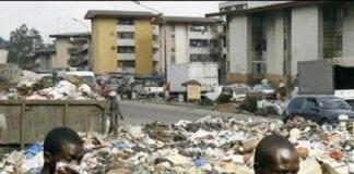 Des citoyens affectés par l'insalubrité se promènent non loin des saletés d'ordures à Conakry