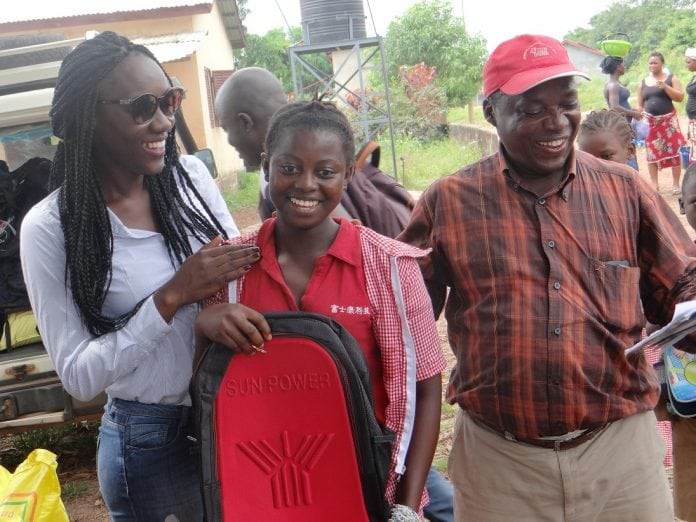 Maimouna Camara, présidente d'Association HOP en train de remettre un sac scolaire à un orphelin d'Ebola à Dubreka