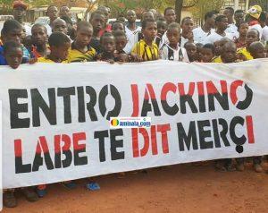 Une bandérole tenue par des jeunes enfant pour remercier le coach Jakino