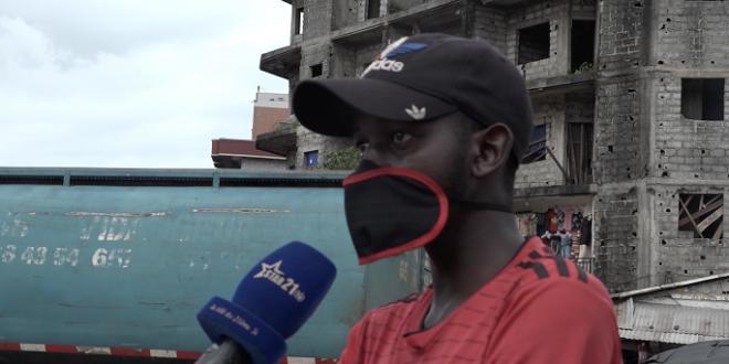 Un citoyen portant un masque s'exprime au micro d'un journaliste